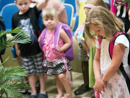 Adyson Markey, age 6, bows her head during a Blessing of the Backpacks Sunday at St. Matthew Evangelical Lutheran Church in York.