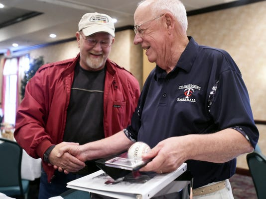 Ken Jones who played from 1967-1969 stands with coach Bob Thomas who shows some of the memorabilia gifts he received Saturday during a retirement party to remember his 51 years coaching Trojan Baseball.