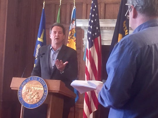 Gov. Steve Bullock, left, answers questions Friday about his executive order regarding dark money.