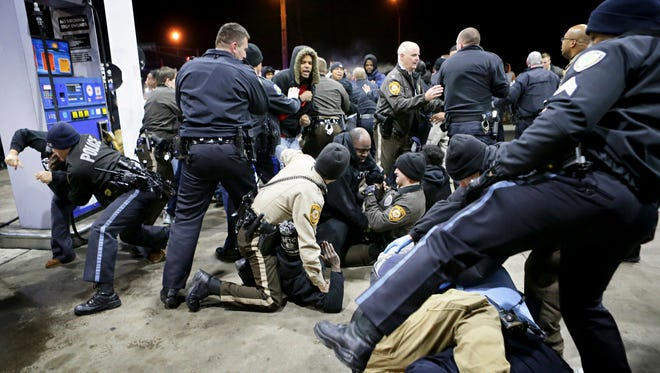 Police try to control a crowd Dec. 24, 2014, on the lot of a gas station following a shooting a few hours earlier in Berkeley, Mo.