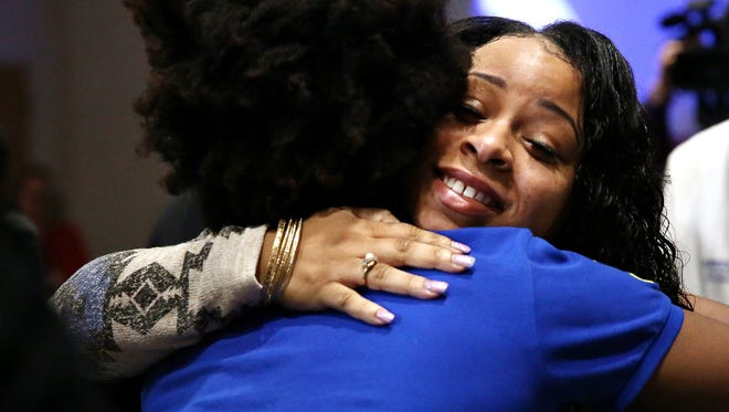 Tiana Carruthers, one of the Kalamazoo mass shooting survivors, briefly stands up to hug a supporter after giving a personal statement at Borgess Medical Center in Kalamazoo on April 14, 2016.