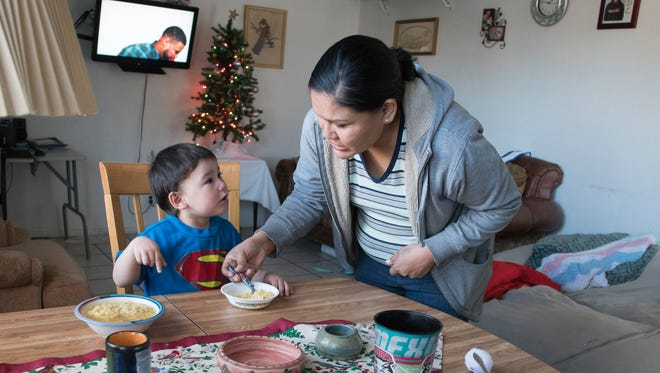 Rhonda Ramirez feeds her son Josiah Lucero, 2, in Albuquerque. Ramirez and Lucero live in the city's International District, one of the poorer neighborhoods in the state.