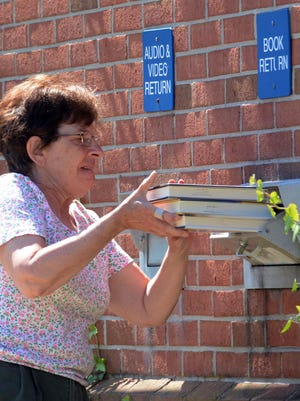 """Christine Haveles of Killingly returns books Monday on the first day inside access is allowed at Killingly Public Library. She said of the first day reopening, """"We have a lot of time on our hands and we need books. Some people don't like reading on the computer and prefer to have a book in their hands."""""""