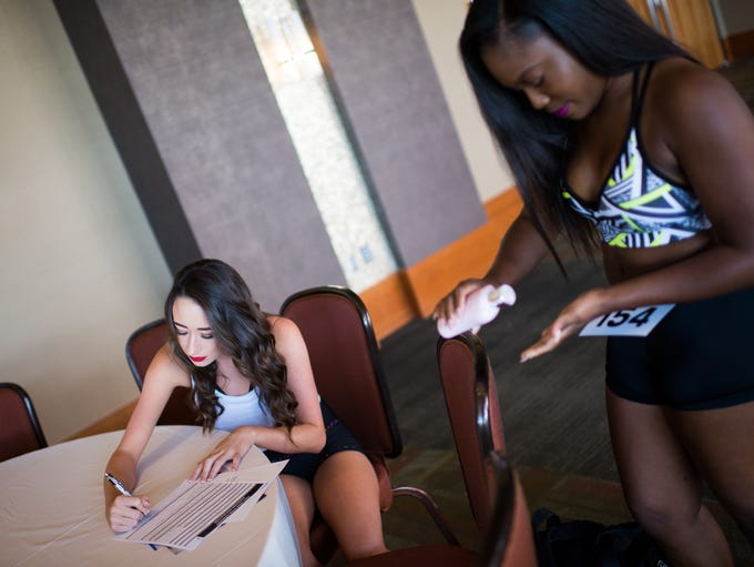 Tara Thurman (left) signs a form while Sydney Thomas