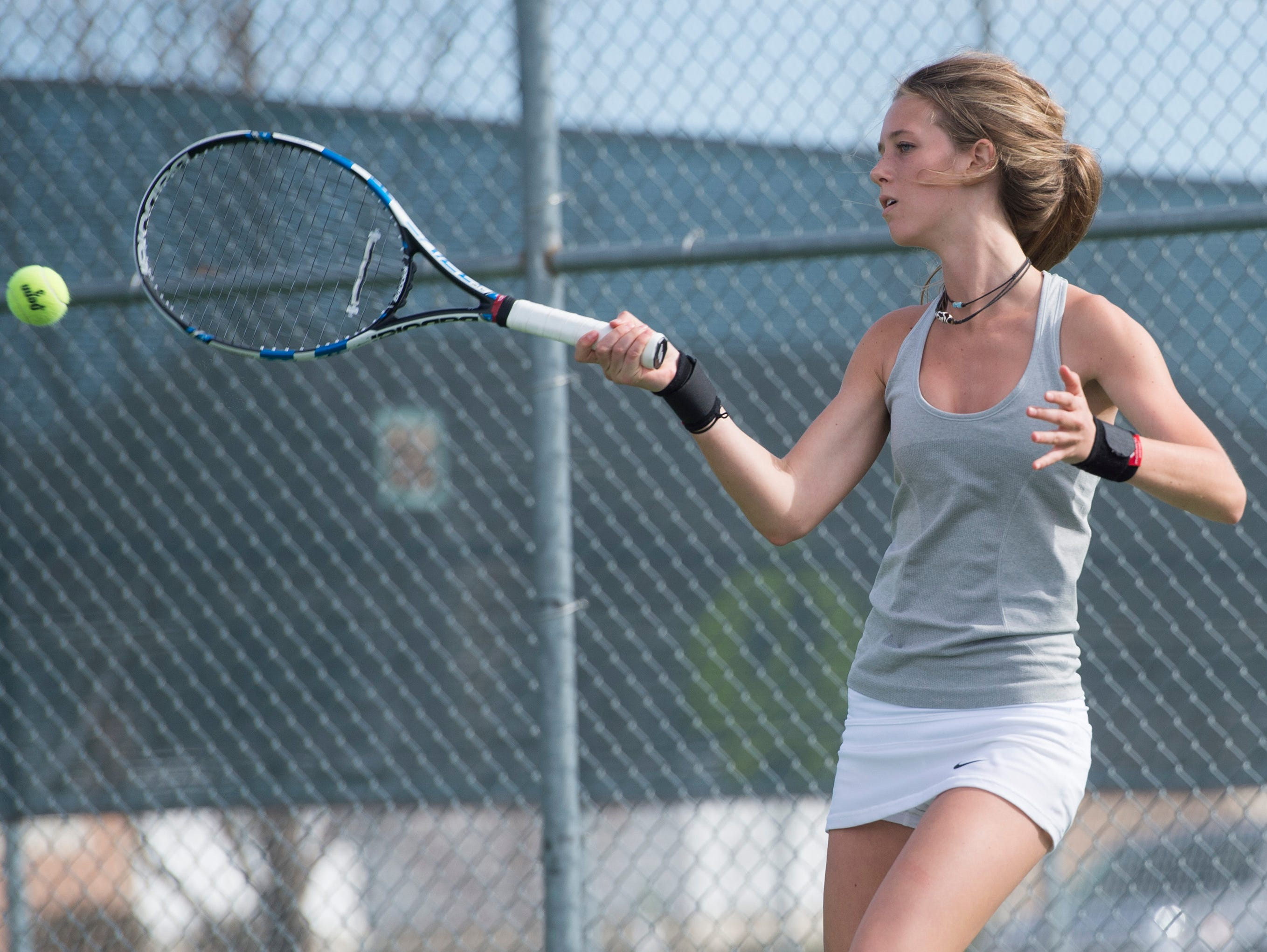 Bailey Koronich of Fossil Ridge High School returns the ball to a Poudre tennis player during a match Wednesday, April 6, 2016.