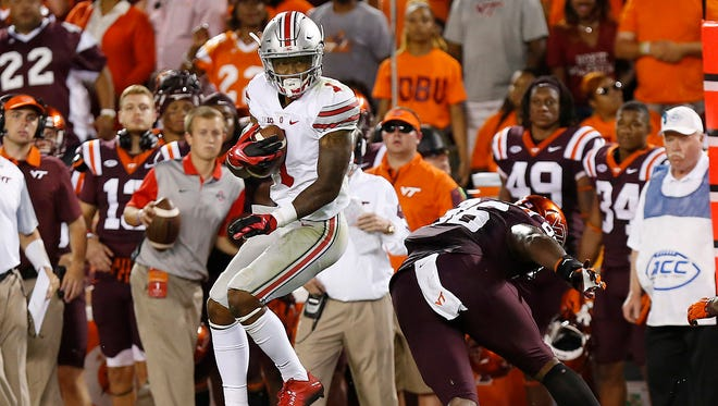Ohio State wide receiver Braxton Miller spins away from Virginia Tech defensive tackle Corey Marshall while running with the ball en route to score a touchdown in the third quarter at Lane Stadium on Monday.