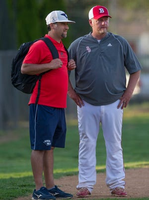 Bosse coach Craig Shoobridge (right) talks with University of Southern Indiana baseball coach Tracy Archuleta after a game against North.
