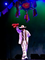 Alejandro Ruiz dances beneath a pinata onstage at the Paramount Theatre.