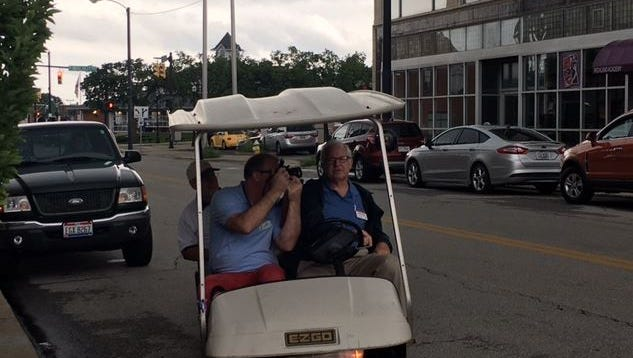 America in Bloom judge Ed Hooker takes a photo downtown Monday as fellow judge Alex Pearl, rear seat, looks on. Mansfield resident Doug Versaw chauffeured the judges.