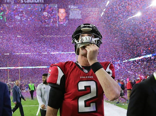 In this photo taken Feb. 5, 2017, Atlanta Falcons quarterback Matt Ryan reacts after losing Super Bowl 51 as the screen flashes New England Patriots quarterback Tom Brady and confetti flies in Houston.  Hey, did you hear the one about Choking Awareness Day? It's held on 3-28. Rimshot, please! Of course, that punch line references the score late in the third quarter of last season's Super Bowl, when it looked as though the Atlanta Falcons would finally win their first championship. (Curtis Compton/Atlanta Journal-Constitution via AP)