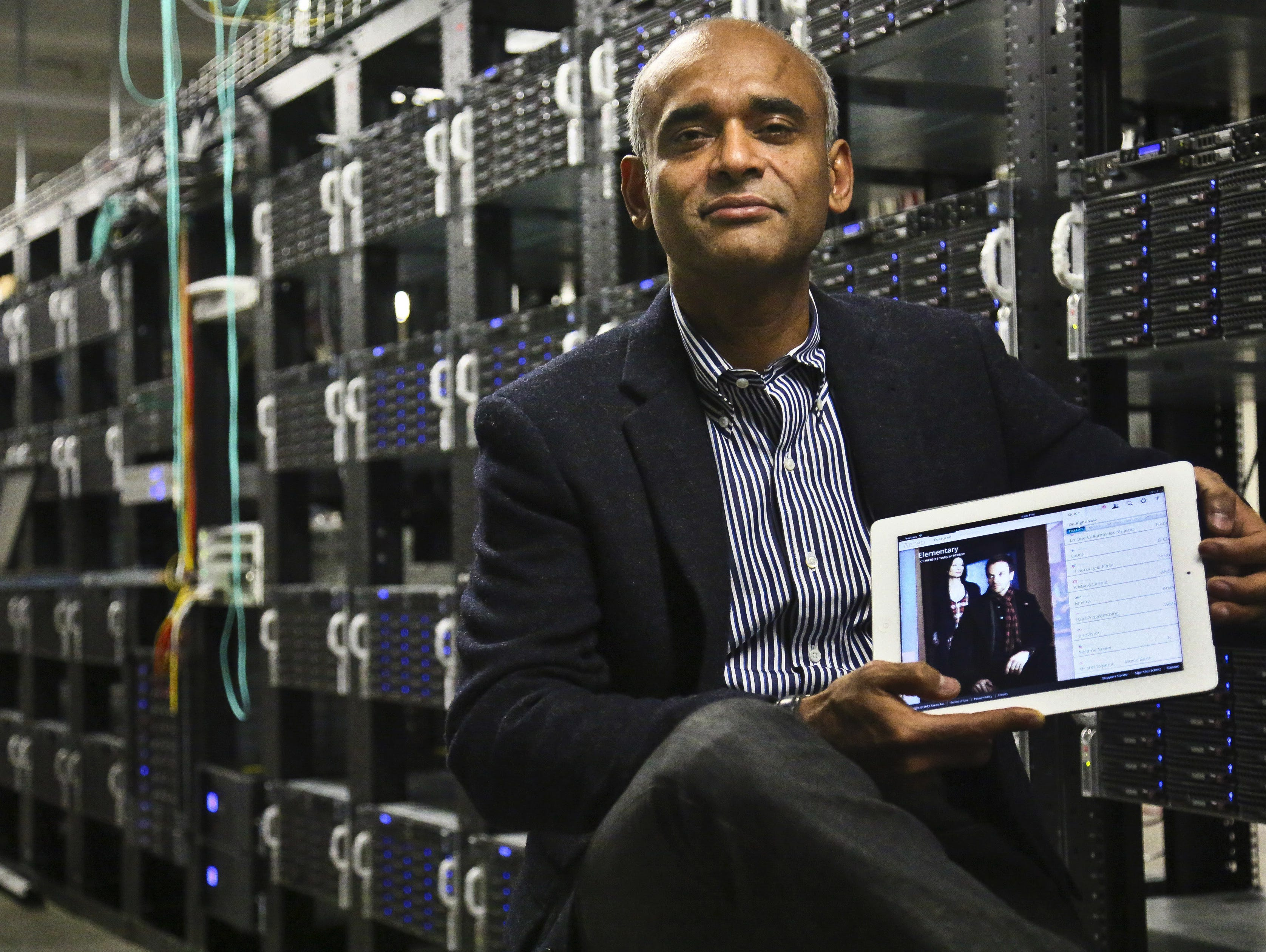 This Dec. 20, 2012 file photo shows Chet Kanojia, founder and CEO of Aereo, Inc., holding a tablet displaying his company's technology, in New York.  The Supreme Court has ruled that a startup Internet company has to pay broadcasters when it takes te