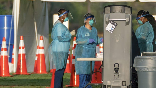 Health-care workers prepare to test people people at the drive-through COVID-19 testing location at the FITTEAM Ballpark of The Palm Beaches on March 31.