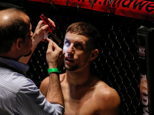 Allen Case of Des Moines, a bantamweight MMA fighter, has his right eye looked at by medical staff after an inadvertent eye poke in his fight with Nathan Endres of St. Charles during the Midwest Cage Championships Thanksgiving Throwdown on Wednesday, Nov. 25, 2015, in Des Moines.