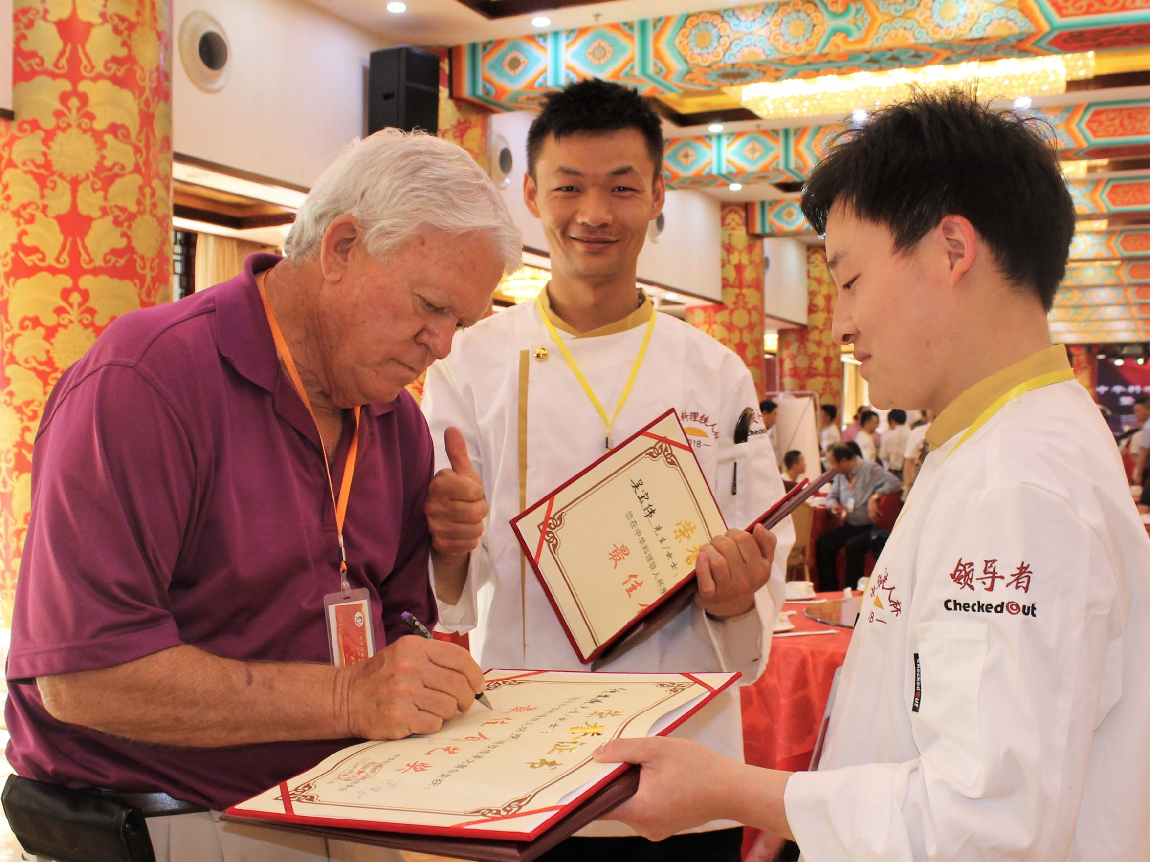 Melvin Martin autographs diplomas of graduating chefs. Martin and his wife, MaryAnn, were considered celebrities during their visit to China in May.