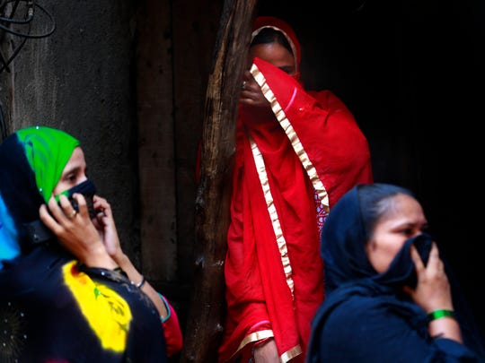 Sex workers cover their faces from cameras as they watch an AIDS awareness event in a red light area on the eve of World AIDS Day in Mumbai, India, Thursday, Nov. 30, 2017.