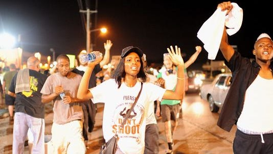 Demonstrators walk and display signs during a peaceful protest on West Florissant Avenue in Ferguson, Missouri, on Aug. 23, 2014, two weeks after the fatal shooting of Michael Brown.