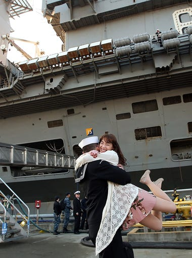 """USS Nimitz Logistics Specialist 3rd Class Michael Zegarra swings his wife Caterina into the air as they embrace on the pier at Naval Base Kitsap-Bremerton on Sunday, December 10, 2017. The couple were the """"First Kiss"""" as Zegarra disembarked the aircraft carrier."""