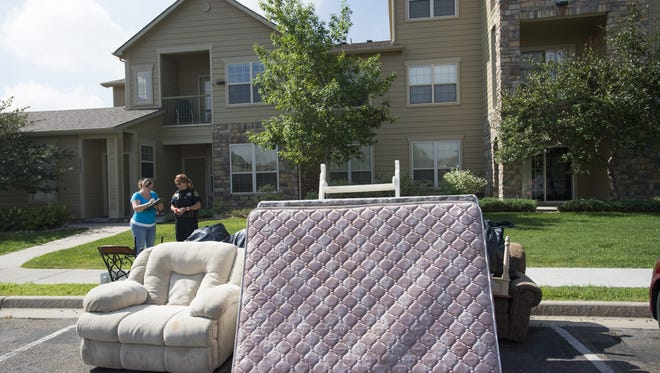 Larimer County Sheriff's Deputy Barb Bowman hands paperwork to a homeowner after a tenant was evicted from a condo in south Fort Collins in this Coloradoan file photo from July 2017.