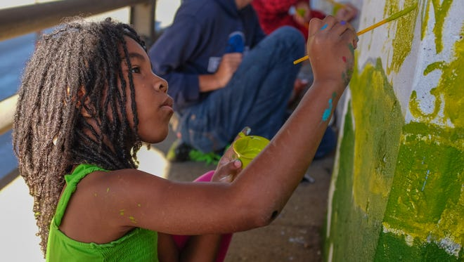 Mary Wilson, 6, does her part on the paint-by-number mural project going on underneath the train bridge across Pennsylvania Avenue near the entrance of Potter Park Zoo Sunday, Oct. 22, 2017.
