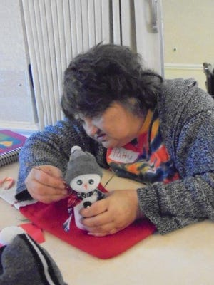 During a Decembervisit to Heartlandby garden club members, resident Patty considers where to place a snowman's right twig arm.