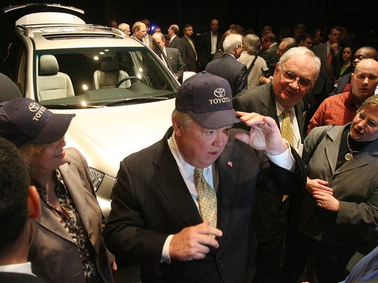 Miss. Gov. Haley Barbour dons a Toyota cap with a Highlander hybrid behind him during a news conference Feb. 27, 2007, at Tupelo High School, where Toyota announced plans to build a Highlander vehicle assembly plant by 2010. The site of the plant is in Blue Springs, about 10 miles from Tupelo, Mississippi.