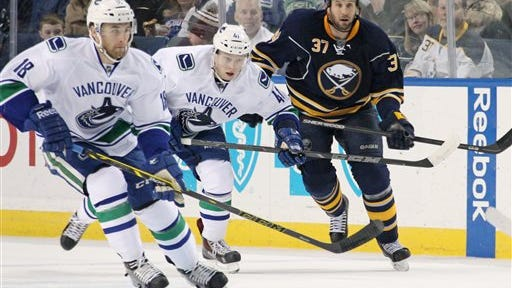 Buffalo Sabres' Matt Ellis (37) and Vancouver Canucks' Ryan Stanton (18) and Ronalds Kenins (41), of Latvia, follow the puck during the first period of an NHL hockey game Thursday, Feb. 26, 2015, in Buffalo, N.Y. (AP Photo/Jen Fuller)