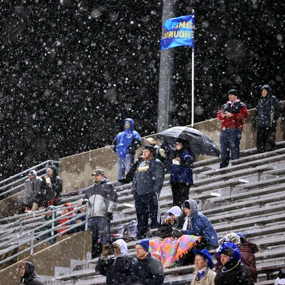 Carmel High School football fans sit through a blast of snow flurries in the first half of Friday night's game against Fishers High School on Oct. 31, 2014.
