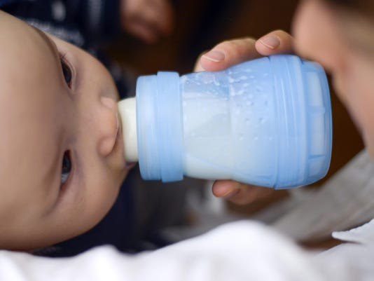 Baby drinking milk out of bottle.