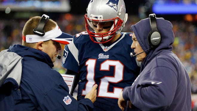 Jan 18, 2015; Foxborough, Mass.; New England Patriots quarterback Tom Brady (12) talks with coach Bill Belichick and offensive coordinator Josh McDaniels during the second quarter against the Indianapolis Colts in the AFC Championship Game at Gillette Stadium.
