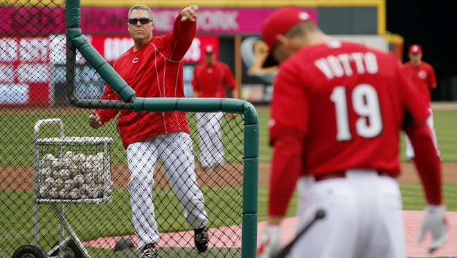 Reds manager Bryan Price throws batting practice as first baseman Joey Votto warms up ahead of the Opening Day game against the Pittsburgh Pirates, Monday, April 6, 2015, at Great American Ball Park in Cincinnati, Ohio.