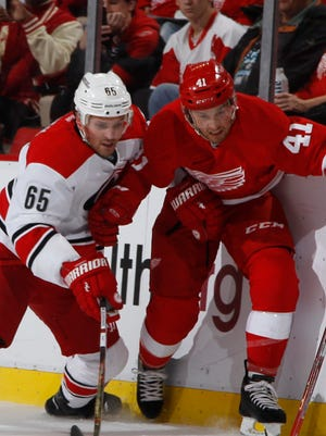 Red Wings forward Luke Glendening and the Hurricanes' Ron Hainsey fight for the puck along the boards in the first period on Tuesday at Joe Louis Arena.