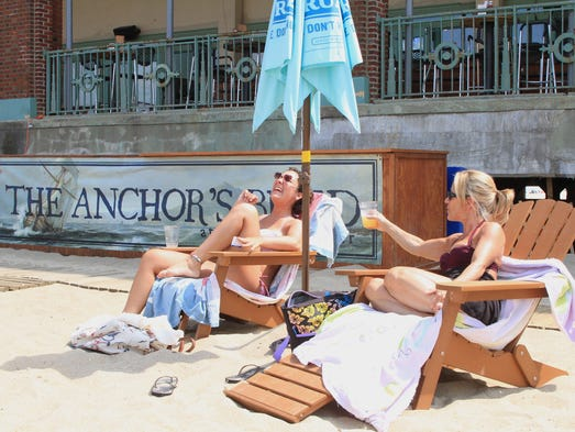 ASB 0710 BEACH BAR  Ann DeFalco, right, of Scotch Plains, salutes her daughter Gina, 22, with a beer, while the two relax on the beach at  The Anchor's Bend new bar area where patrons can drink alcohol in the sand in Asbury Park, Wednesday, July 9, 2014. Photographer/Mary Frank