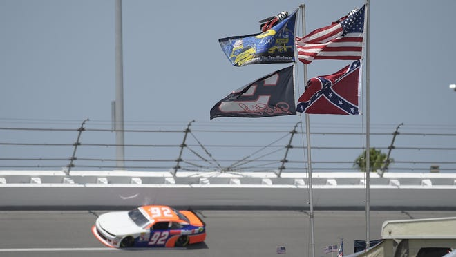U.S., Confederate and Dale Earnhardt Sr. and Jr. flags fly near Turn 4 during NASCAR qualifying at Daytona International Speedway in 2015. NASCAR banned the Confederate flag from its races and venues Wednesday.