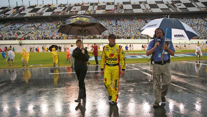 Driver David Gilliland, center, walks back to the garages after driver introductions the NASCAR Sprint cup Series auto race at Daytona International Speedway in Daytona Beach, Fla., on Saturday. Gilliland is on the pole for the race, which has been postponed until Sunday because of the inclement weather.