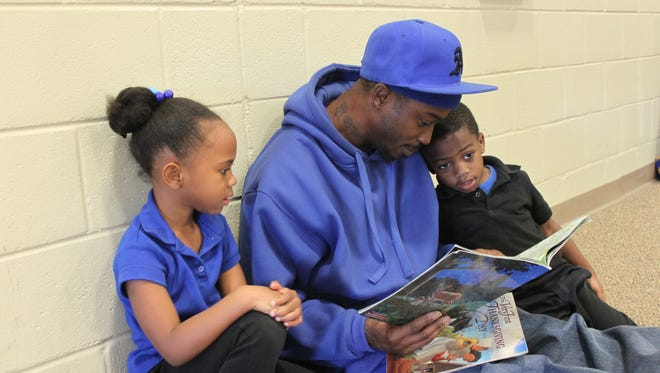 Marquel Horton reads to his children Cekaira Anderson, 6, and Marqavion Horton, 4, during 'Donuts with Dads' at Denmark Elementary School.