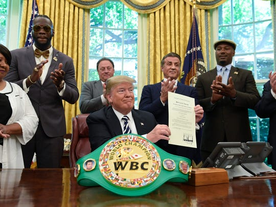 President Donald Trump posthumously pardons Jack Johnson, boxing's first black heavyweight champion, during an event May 24 in the Oval Office of the White House in Washington. Trump is joined by, from left, Linda Haywood, who is Johnson's great-great niece, heavyweight champion Deontay Wilder, Keith Frankel, Sylvester Stallone, former heavyweight champion Lennox Lewis and World Boxing Council President Mauricio Sulaimán.