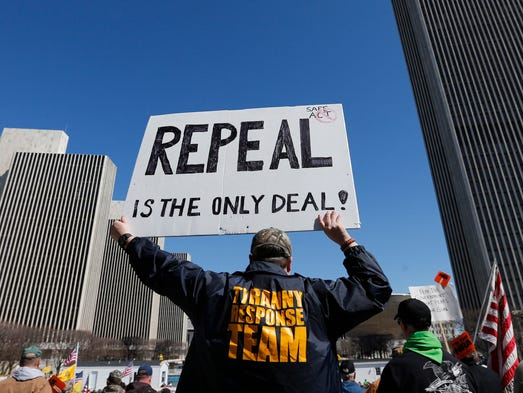 A gun rights activist holds a sign during a rally at the Empire State Plaza on Tuesday, April 1, 2014, in Albany.
