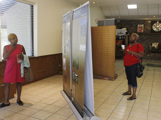 """Eleanor Simms, left, and Renee Burley-Anderson walk through the """"Free at Last!"""" exhibit at the West Tennessee Delta Heritage Center."""