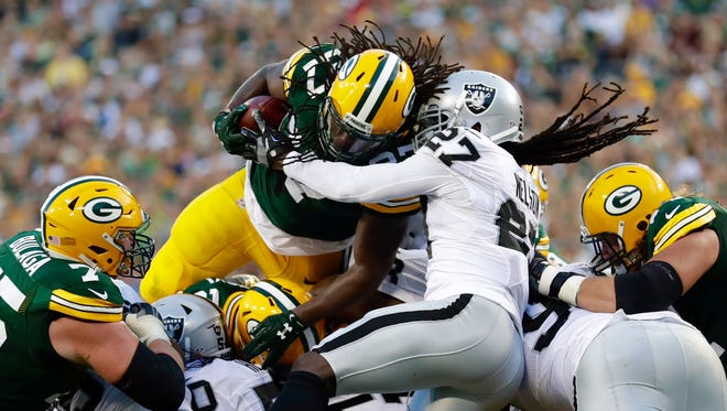 Packers running back Eddie Lacy breaks through the line for a 1-yard touchdown in the first quarter against the Raiders at Lambeau Field.
