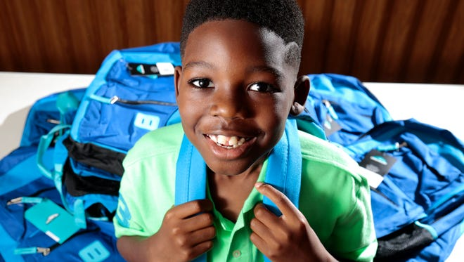 Jeremiah Plummer, 8, poses with a small portion of backpacks he plans to donate at  Southern Baptist Church in the Avondale neighborhood of Cincinnati on Thursday, July 28, 2016. Plummer originally set out to raise enough money for 100 backpacks to donate to homeless children, but with help from friends, family and social media, he was able to purchase more than 200. The book bags will be distributed Saturday to those in need in Over-the-Rhine.
