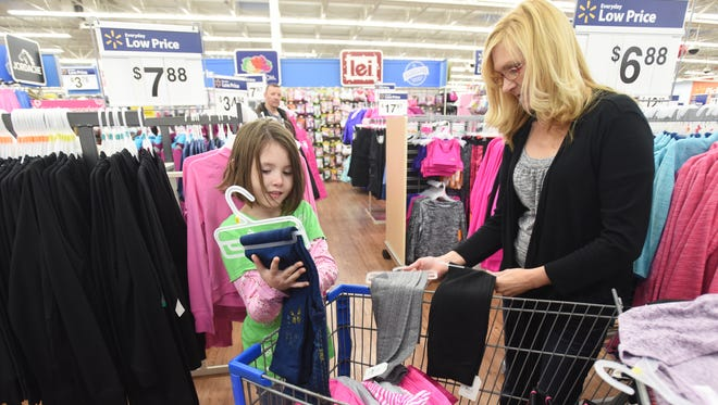 Kylie Greenawalt picks a pair of pants while shopping with Kim Roof duringt he Salvation Army Christmas Castle event on Monday.