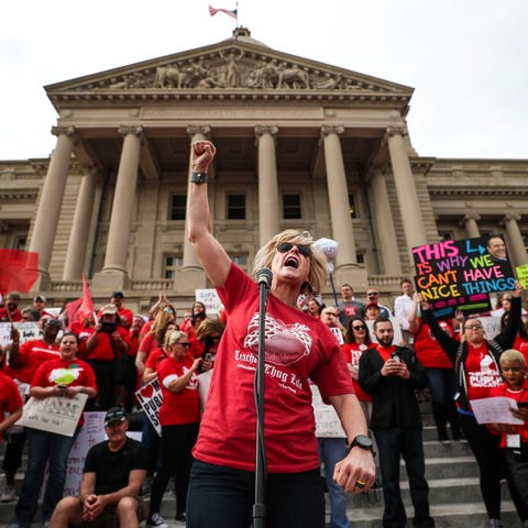 Teacher Robin Burr leads a chant to during...