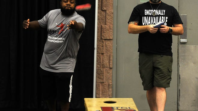A.J. Sims (left), from Caldwell, tosses a beanbag while Thomas Scoggins (right), from Mesquite, waits to throw during the Texas Cornhole League State Championship on Saturday, June 24, 2017, at the Abilene Convention Center.