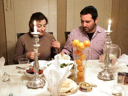 Elizabeth Suazo, left, and her husband Maximiliano Herrera-Monasterio enjoy dinner on the first night of Hanukkah Tuesday at the new Chabad at Purdue center in West Lafayette.
