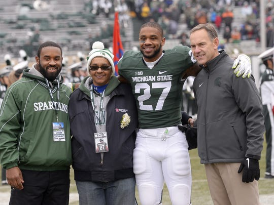 MSU football coach Mark Dantonio poses former player