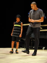 John Manzari, 22, right, teaches a dance combination to Maximus Klevence, 10, of Secane, Pennsylvania, during a rehearsal at the Delaware Theater Company in Wilmington.