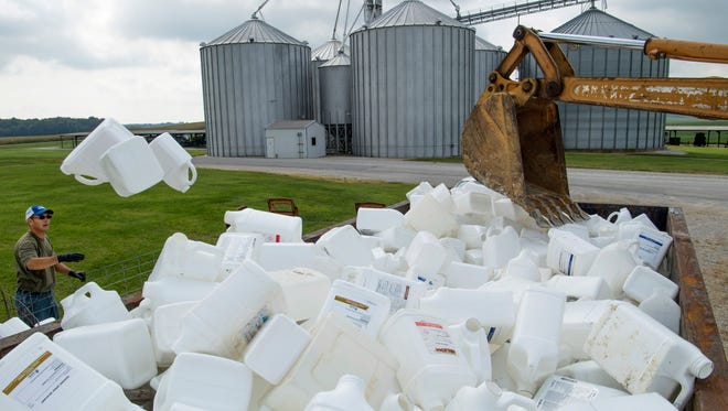 Daniel Smith tosses empty chemical containers into a dumpster to be recycled at the annual Chemical Rinse and Return Jug Day at Scott Farms near Zion, Ky., Tuesday morning.