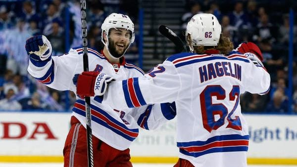 Derick Brassard of the Rangers celebrates with Carl Hagelin after scoring a goal on an empty net against the Tampa Bay Lightning during the third period in Game Six of the Eastern Conference Finals during the 2015 NHL Stanley Cup Playoffs at Amalie Arena on May 26, 2015 in Tampa, Florida.