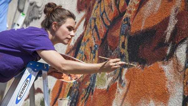 Justine Peterson, Utah Online School art teacher and professional artist, works on the mural Wednesday at the Red Cliffs Desert Reserve Visitor Center, 10 N. 100 East.