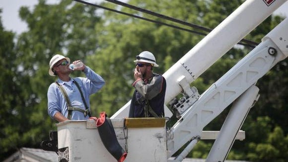 Two Delmarva Power workers take a quick break to hydrate while working in high temperatures.